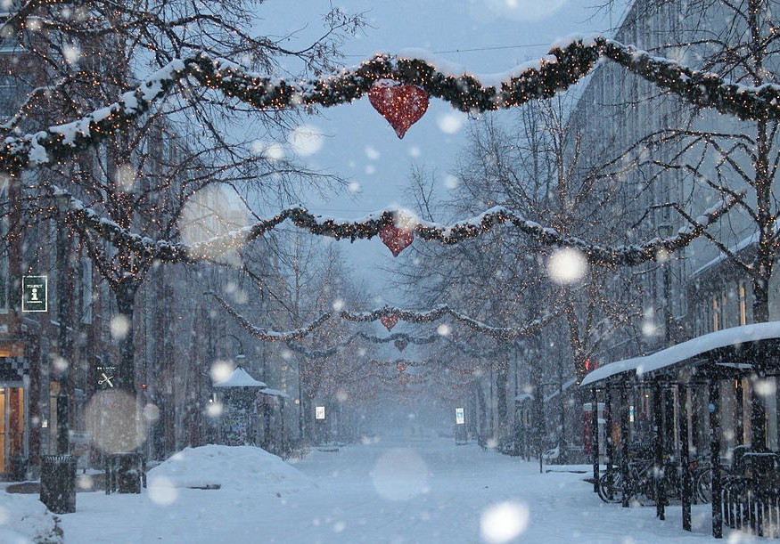 snow falling in a street decorated for christmas
