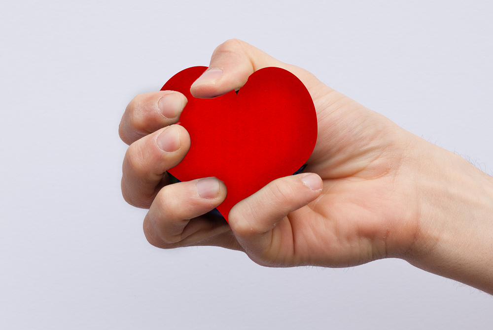 squeezing a heart shaped stress ball