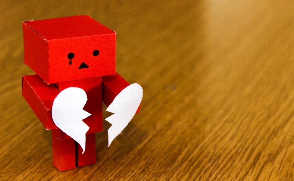 red paper block robot holding two halves broken heart